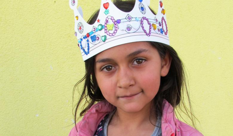 Pieni romanityttö kruunu päässään.