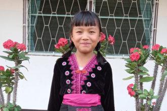 Lettipäinen tyttö hymyilee.