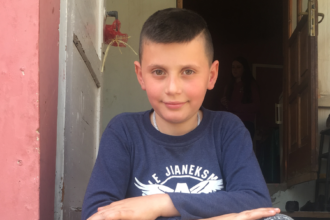 Albanialaispoika istuu kuistin portailla.