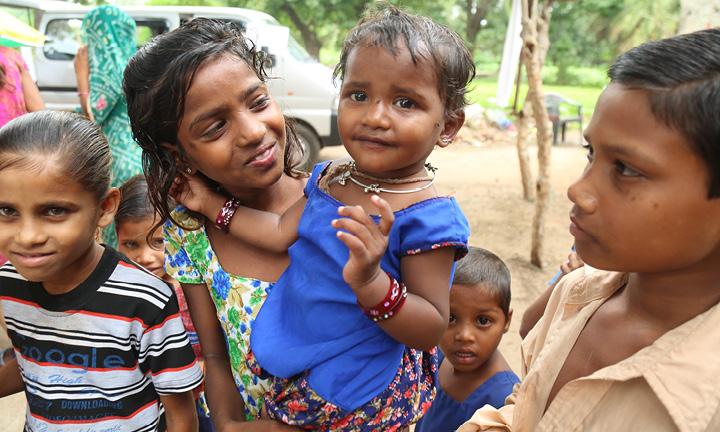 Iloisia lapsia. Isompi tyttö pitää pienempää lasta sylissä.