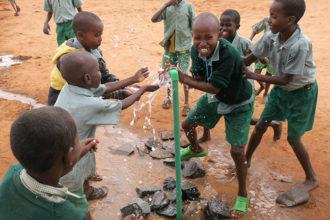 Lapset iloitsevat vesipisteen luona