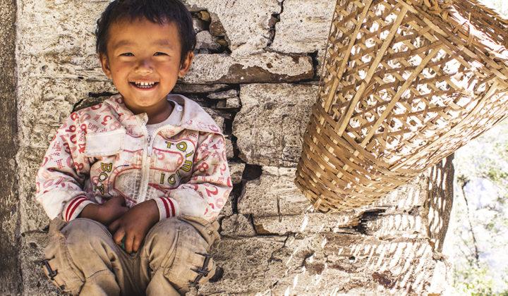 Pieni poika istuu maassa nauraen.