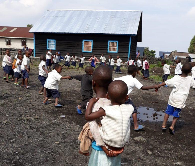 Tyttö ja pieni lapsi koulun pihalla Kongossa