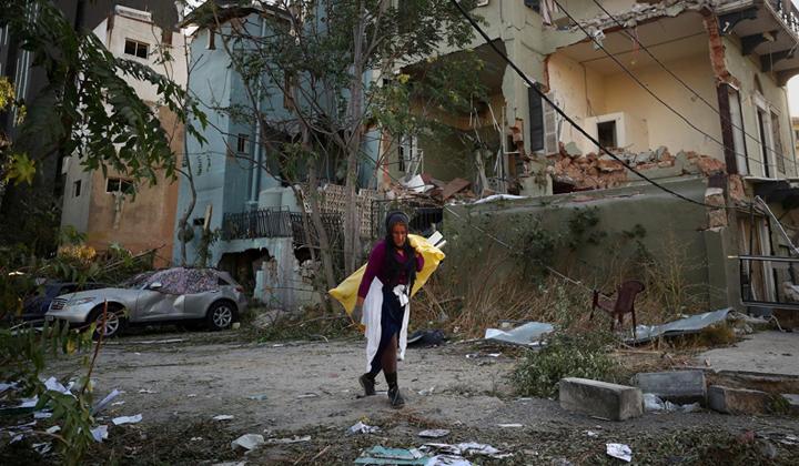 Kuvassa beirutilainen nainen kulkee raunioituneen talon ohi