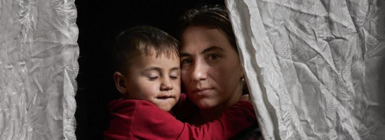 Nainen, jonka sylissä on lapsi silmät kiinni, näkyy osittain verhon takaa.
