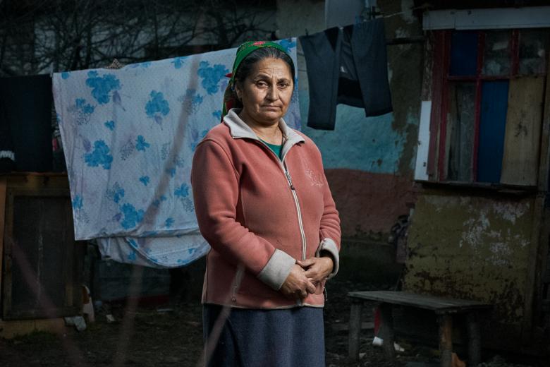 Huivipäinen nainen seisoo pyykkinarulla roikkuvien kankaiden edessä.