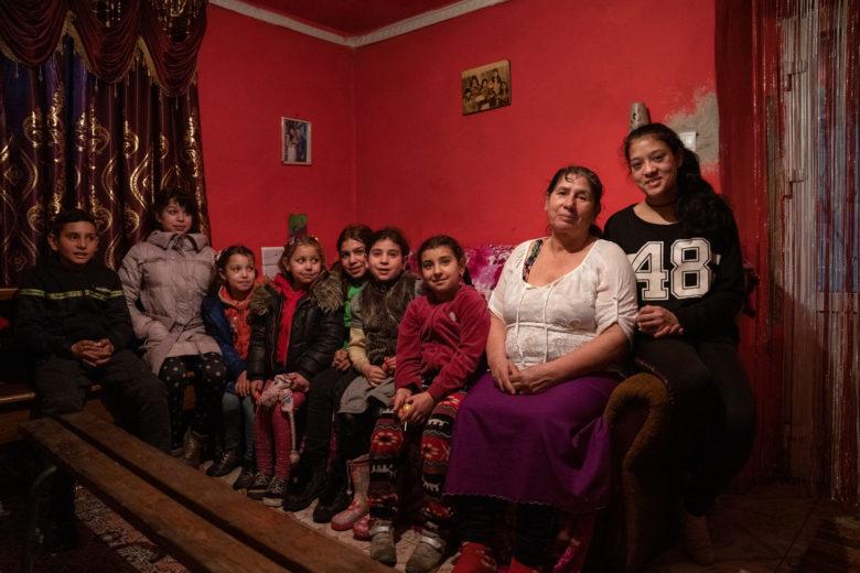 Ukrainalainen Vera istuu pienen kotinsa sängyllä lastensa ja lastenlastensa kanssa.