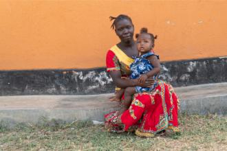 Äiti istuu lapsi sylissä oranssin seinän vieressä.