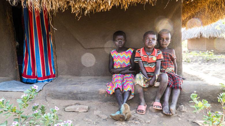 Kolme lasta värikkäissä vaatteissa istuu savimajan edessä Bidibidin pakolaisalueella Ugandassa.
