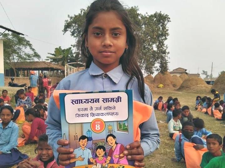 Nepalilainen koulutyttö koulupuvussa pitää kädessään värikästä oppikirjaa.