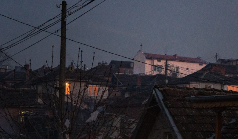 Kuvassa näkyy pimeässä hohtava ikkuna ja kirkon risti illan hämärässä slummissa Bulgariassa.