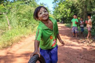 Kuvassa myanmarilainen pieni poika vierittää kumirengasta tiellä.