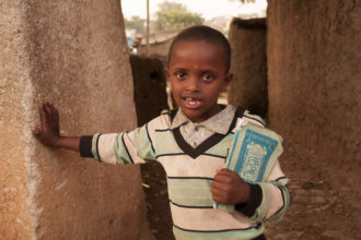 Etiopialainen pieni poika raidallisessa paidassa nojaa seinään kirjoja kainalossaan.