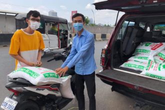 Kaksi kambodzalaista miestä kasvomaskit kasvoilla pakkaavat ruokasäkkejä autoon.