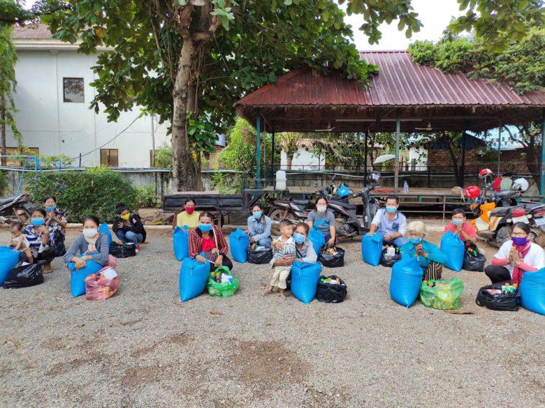 Kambodzalaisia naisia ja lapsia istumassa rakennuksen edessä kasvomaskit kasvoilla ruokasäkkien kanssa.