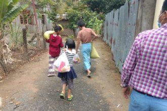 Lapsia kantamassa ruokakasseja.