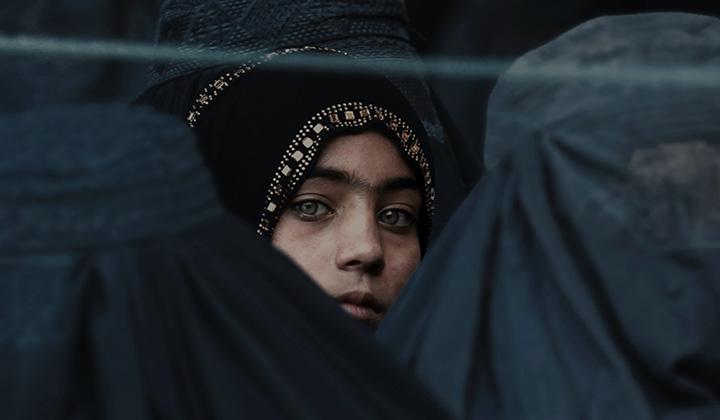 Afganistanilainen tyttö burkhaan pukeutuneena.