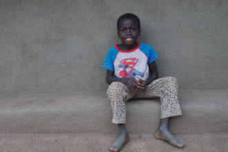 Poika istuu talon seinustalla.