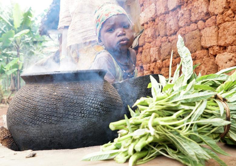 Pieni lapsi katsoo kameraan ruokapadan takaa.