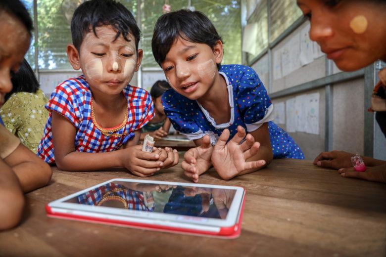 Ryhmä lapsia katsomassa tablettia joka on pöydällä.